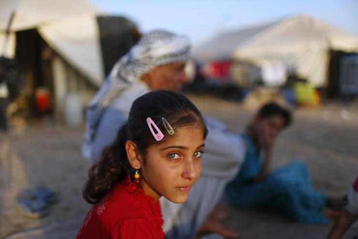 In this photo, a displaced Iraqi child, who fled from Islamic State violence in Mosul, sits with her family outside their tent at Baherka refugee camp in Erbil September 14, 2014. Reuters/Ahmed Jadallah