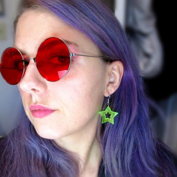 woman wearing green neon star cutout statement earrings