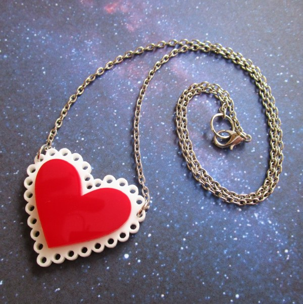 red heart necklace with chain in curl to show lobster claw clasp on space background