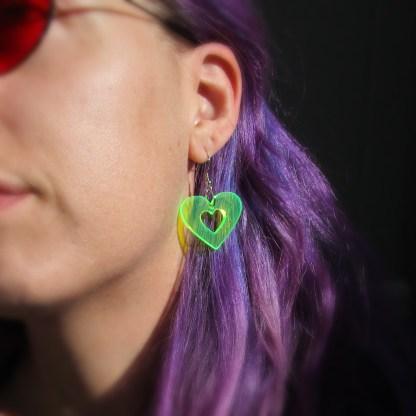 lady wearing neon green heart rave earring