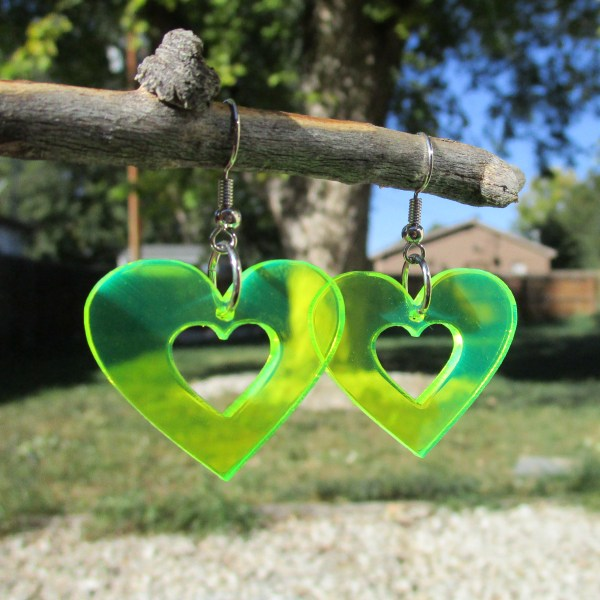 glowing neon green heart shaped dangle earrings hanging on stick to show transparency