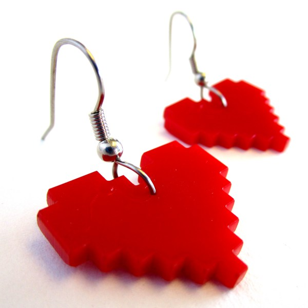 closes up side view of red 8 bit pixel earrings with hooks on white background