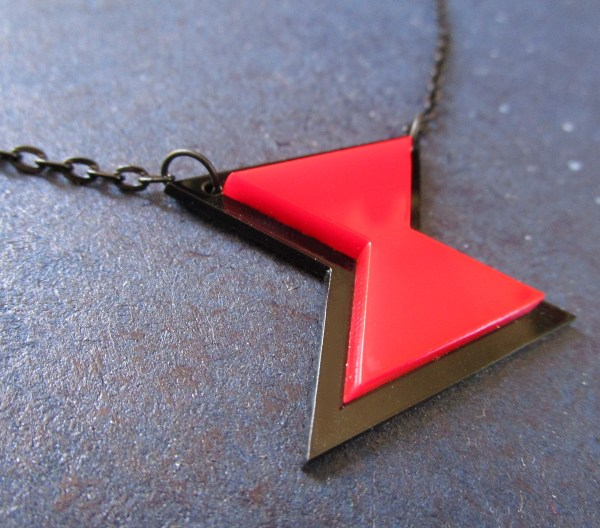 side view of close up black widow symbol pendant necklace red and black hourglass with chain