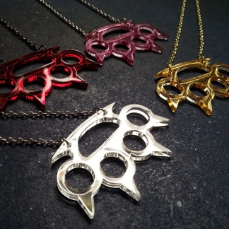 sideways close up of four brass knuckle with claw shape pendant necklace, one red, one silver, one gold and one pink
