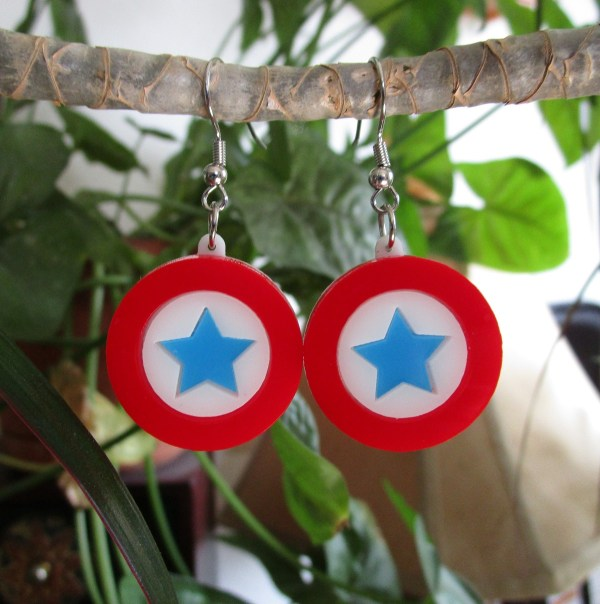 Captain America Mini Shield Earrings in red white and blue hanging from plant