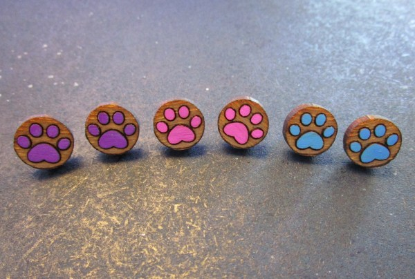 line of paw print earrings in purple pink and blue on space background