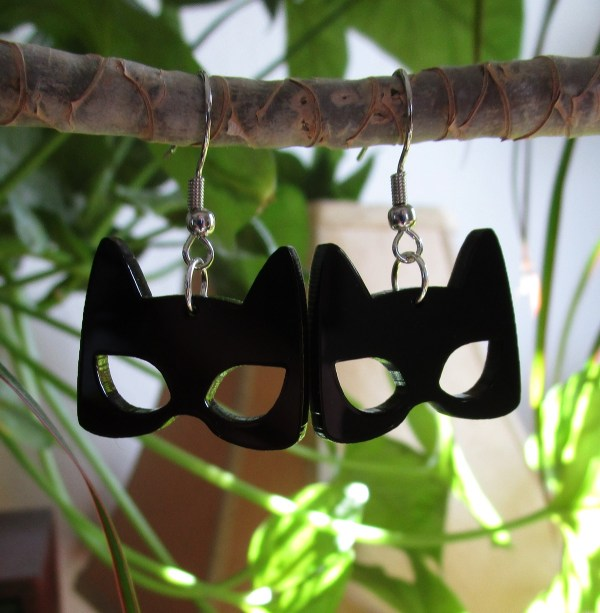 cat mask shapped earrings hanging on plant