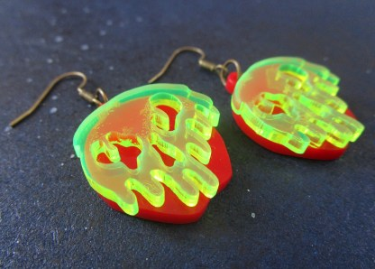 close up side shot of snow white poison apple earrings
