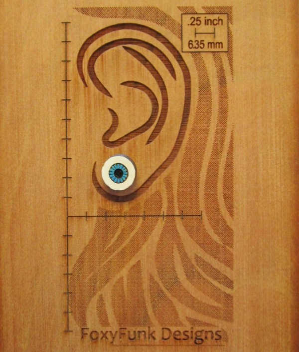 wood bard etched out in shape of ear with blue eyeball earring