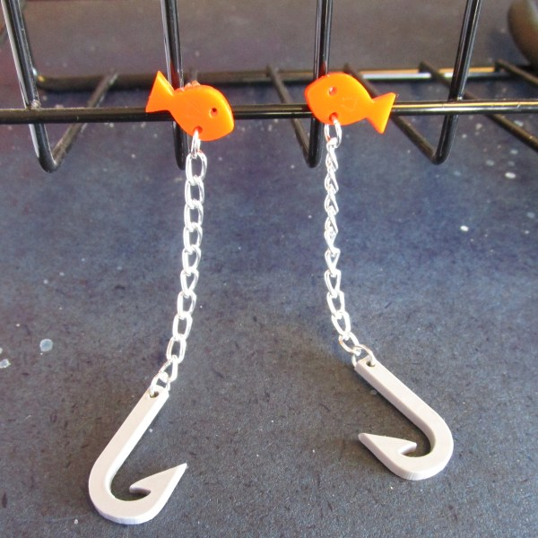 hook and gold fish dangle stud earrings hanging off wire