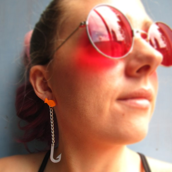 woman in red glasses looking right wearing goldfish and hook earrings