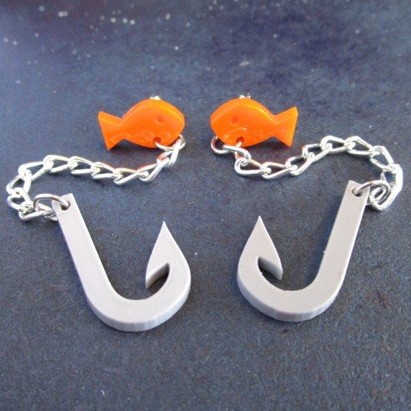 close up of goldfish chain and hook earrings laying on space background
