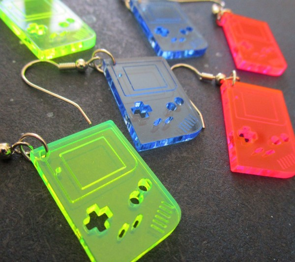 gameboy shaped neon earrings in neon green blue and pink laying on blue background