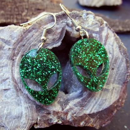 side view of little green alien big eyes head earrings on geode rock