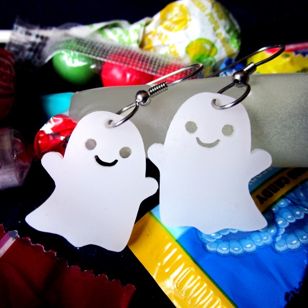happy ghost laser cut pendant earrings on top of candy background