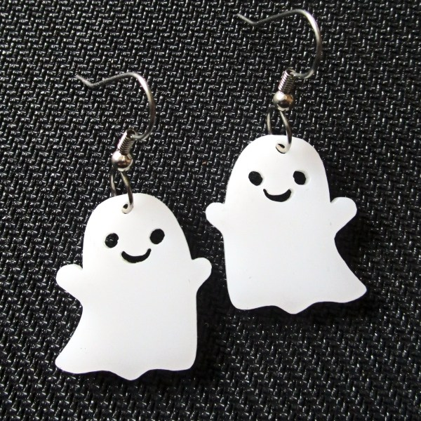 close up of cute smiling ghost dangle earrings on black textured background