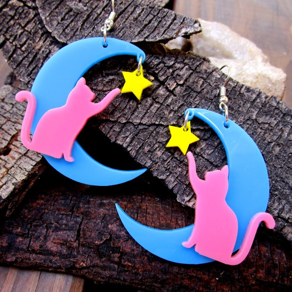 pink cat blue moon yellow star dangle earrings with wood bark background