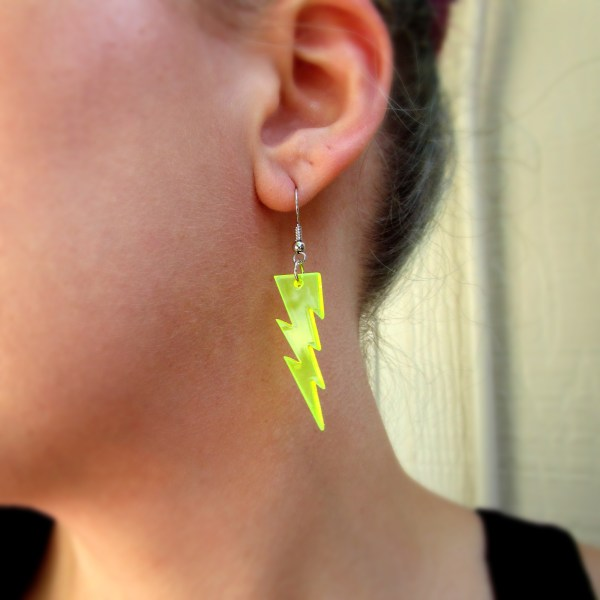 close up of womans ear wearing neon lightning bolt dangle earring