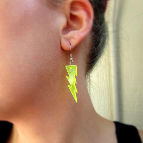 close up of womans ear wearing neon lightning bolt dangle earring