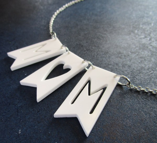 up close view of mom banner necklace on gray background