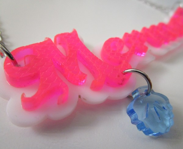 close up of M and shell on pink Mermaid Word Statement Necklace