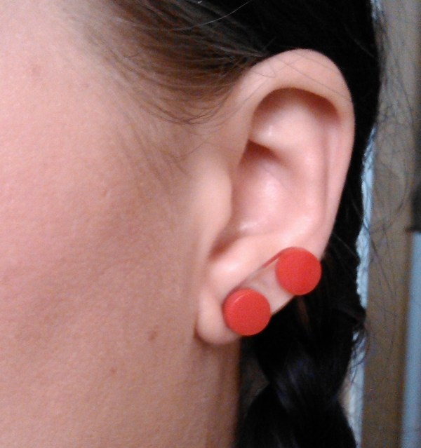 Close up of ear with 2 red circle button earrings