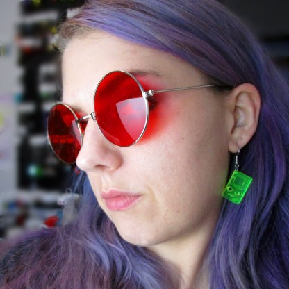 woman in red glasses wearing neon yellow 1st edition handheld gameboy dangle earrings