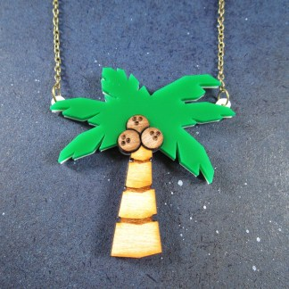 laser cut palm tree necklace laying on space background