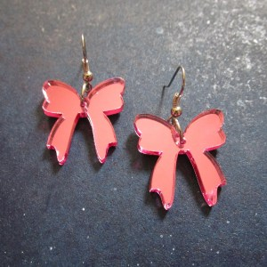 pink ribbon present bow earrings on space background showing french earring hooks