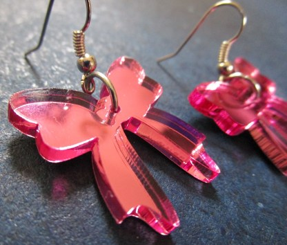 up close shot of mirrored acrylic pink bow earrings