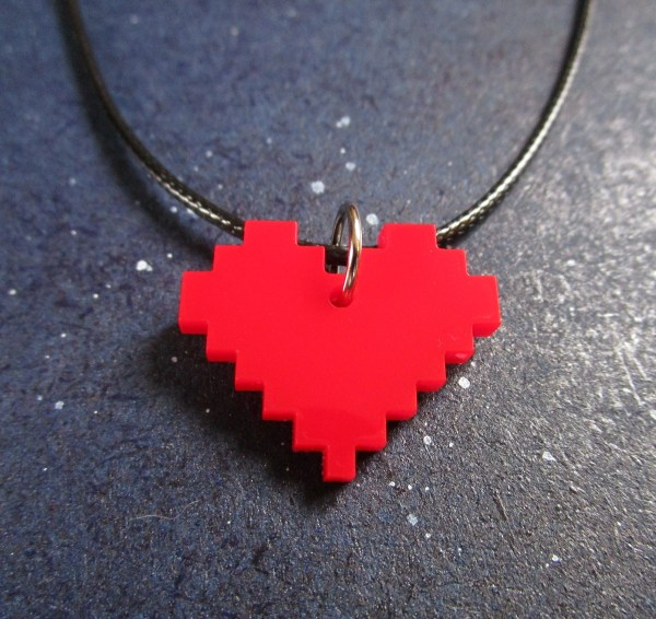 close up of red 8 bit heart necklace on space background