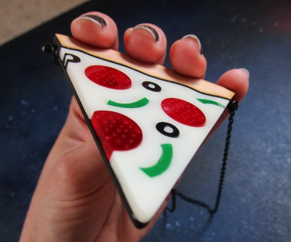 hand holding Pizza Slice Statement Necklace pendant to show size