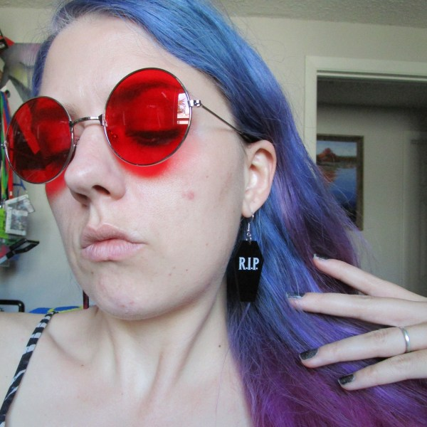 woman in red round glasses and purple hair wearing rip coffin goth earrings