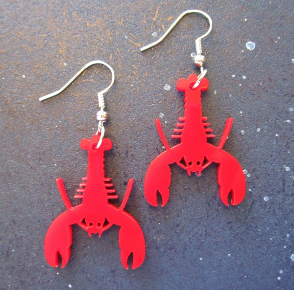 laying down Red Lobster Earrings with french hooks on space background