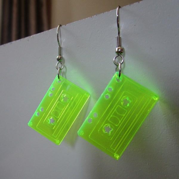 neon green tape cassette dangle earrings hanging on white board