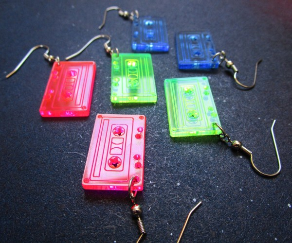 tape cassette earrings laying on dark gray board pair of pink cassettes, green cassettes and blue cassettes