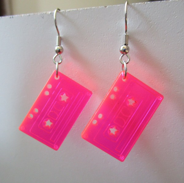 neon pink tape cassette dangle earrings hanging on white board