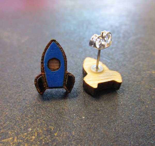 close up of blue rocket ship stud earrings with one facing forward and one on side to shoe post and clutch back