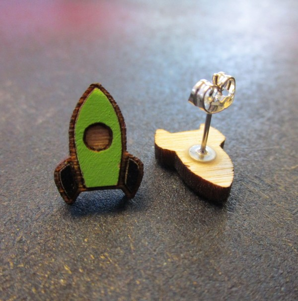 close up of green rocket ship stud earrings with one facing forward and one on side to shoe post and clutch back
