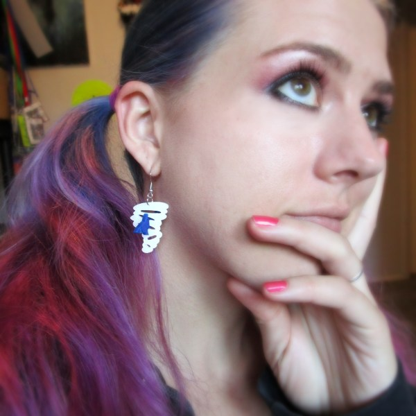 woman with purple hair wearing a blue and white sharknado earring