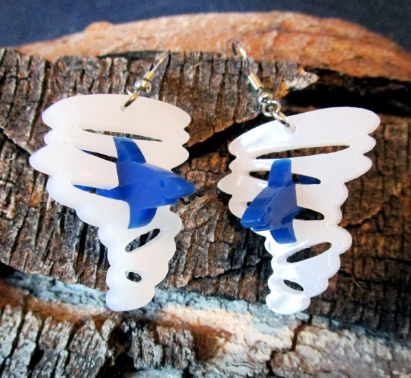 white and blue sharknado pendant earrings laying on wood bark