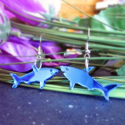 shiny mirrored blue shark earrings hanging on green grass with purple flower in background