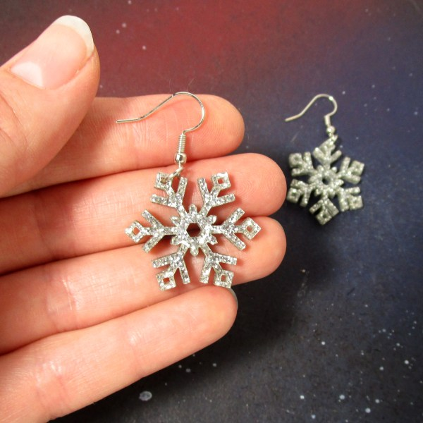 silver glitter snowflake earrings in hand to show size
