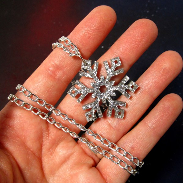 hand holding glitter silver snowflake pendant necklace to show size