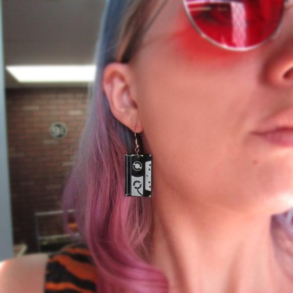 woman wearing tape cassette earring in ear with pink hair