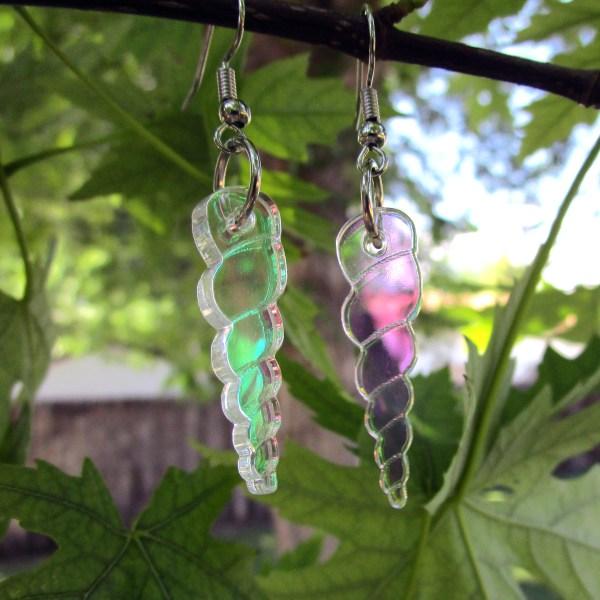 unicorn horn earrings hanging on plant, semi transparent pendants