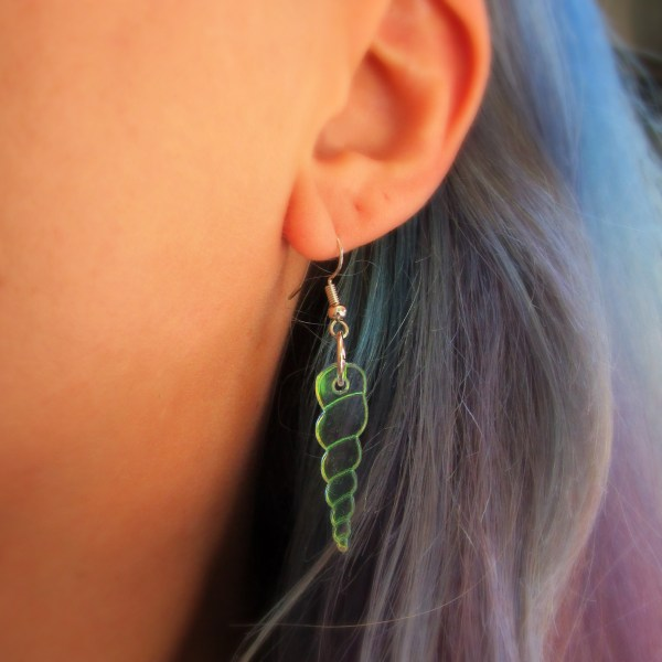 woman ear close up wearing unicorn horn earring