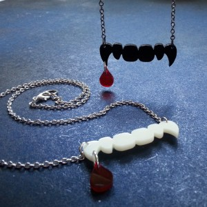 hanging black vampire fand and blood drip necklace and one ivory fang and blode drop necklace on surface