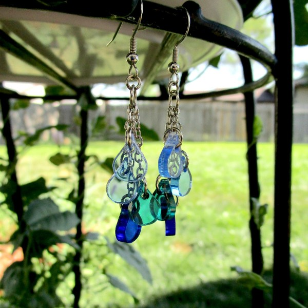 Blue Ocean Water Drops Earrings hanging off metal bar showing green yard background