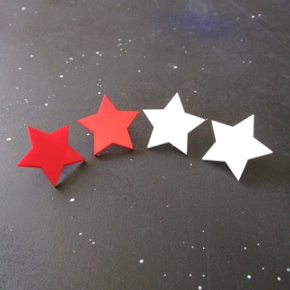 big red and white star stud earrings in row on space background
